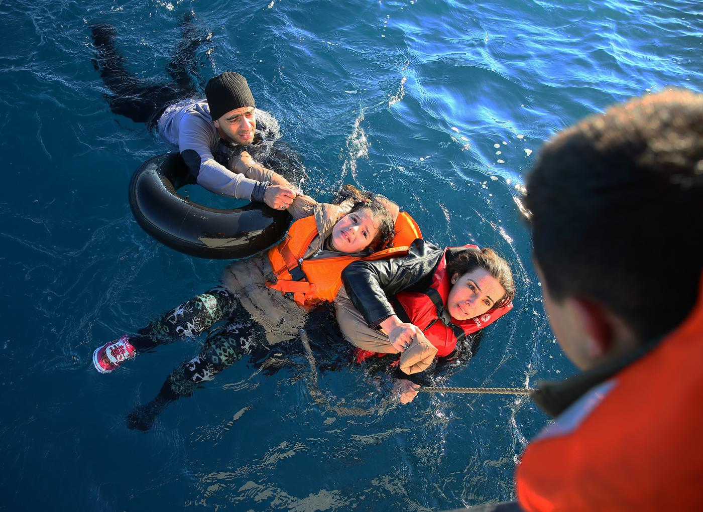 AYDIN, TURKEY - JANUARY 22: Turkish Coast Guard personnel help refugees as they swim with buoys, after they toppled over a fishermen dinghy en route to Greece on January 22, 2016 in Didim district of Aydin, Turkey. 4 refugees body including 3 children pulled out of the water as Turkish coast guard personnel rescued 43 others. (Photo by Emin Menguarslan/Anadolu Agency/Getty Images)