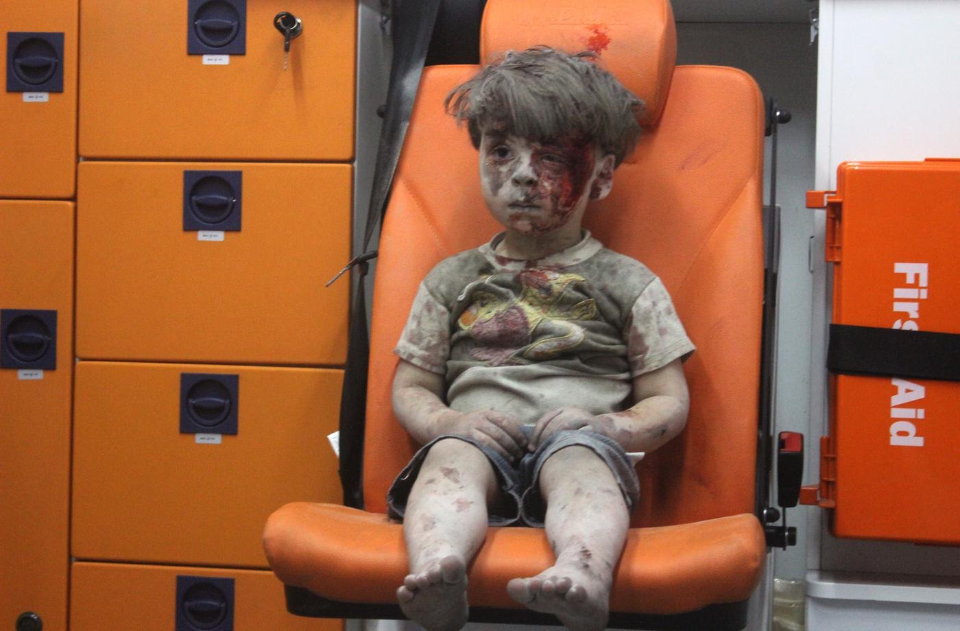 ALEPPO, SYRIA - AUGUST 17: (EDITORS NOTE: Image contains graphic content.) 5-year-old wounded Syrian kid Omran Daqneesh sits alone in the back of the ambulance after he got injured during Russian or Assad regime forces air strike targeting the Qaterji neighbourhood of Aleppo on August 17, 2016. (Photo by Mahmud Rslan/Anadolu Agency/Getty Images)