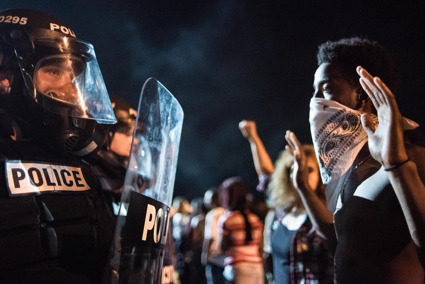 CHARLOTTE, NC - SEPTEMBER 21: Police officers face off with protesters on the I-85 (Interstate 85) during protests in the early hours of September 21, 2016 in Charlotte, North Carolina. The protests began last night, following the fatal shooting of 43-year-old Keith Lamont Scott by a police officer at an apartment complex near UNC Charlotte. (Photo by Sean Rayford/Getty Images)
