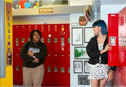 Two non-binary students looking at eachother in a school hallway photoshopped